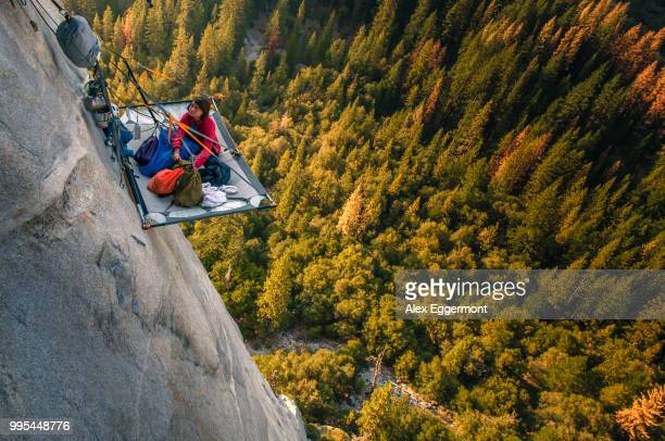 woman looking up from portaledge on triple direct, el capitan, high angle view, yosemite valley, california, usa - yosemite valley stock photos and pictures