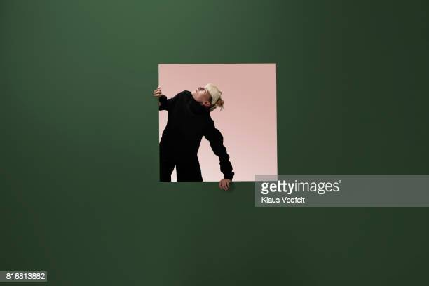 woman looking up, from square opening in coloured wall - caucasian appearance stock pictures, royalty-free photos & images