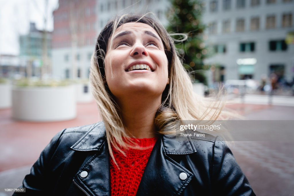 A woman looking up in the sky in the street : Stock Photo