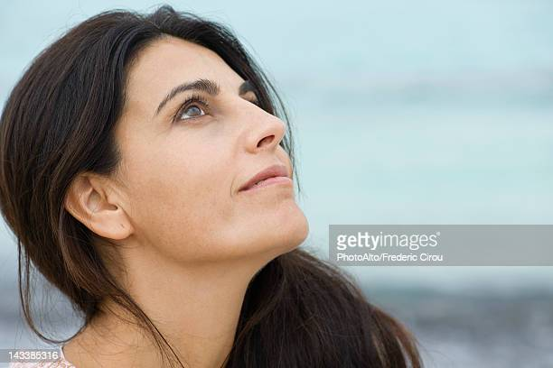 Woman looking up in thought, portrait