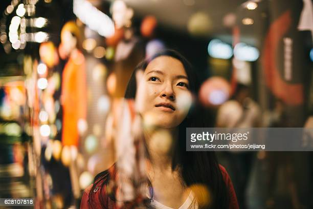a woman looking up into a shopping window - シンガポール市 ストックフォトと画像