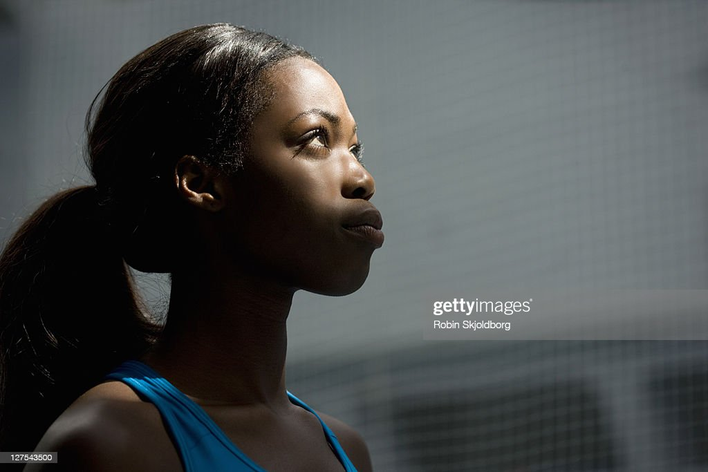Woman looking up into light : Stock Photo