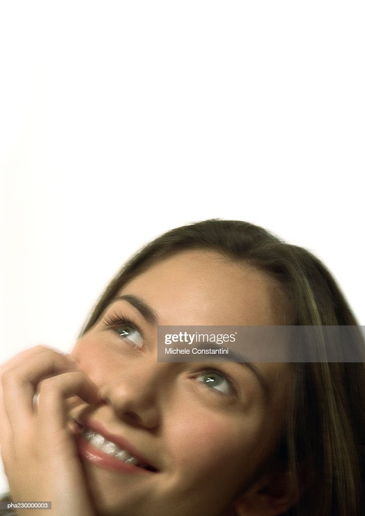 Woman looking up smiling, hand on face, portrait. : Stockfoto