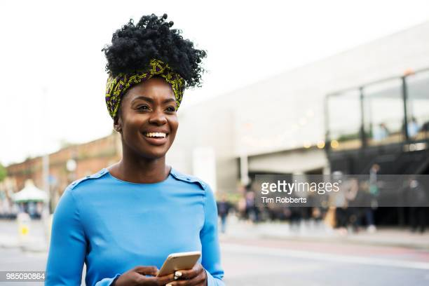 Woman looking up using smart phone on street.