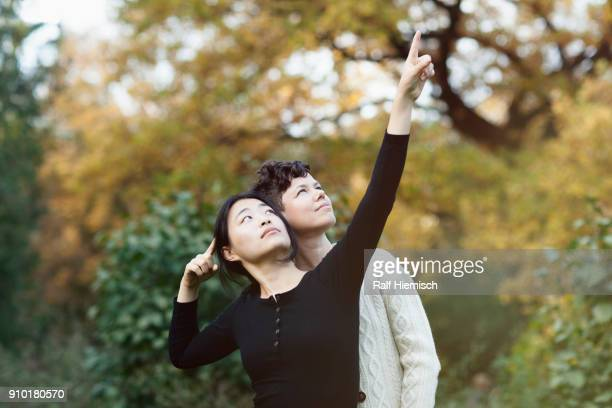Woman looking up while pointing and showing to friend at park