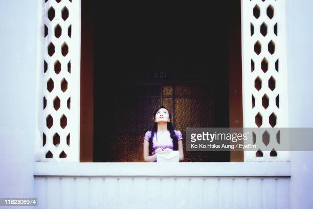 woman looking up while standing by window - ko ko htike aung stock pictures, royalty-free photos & images