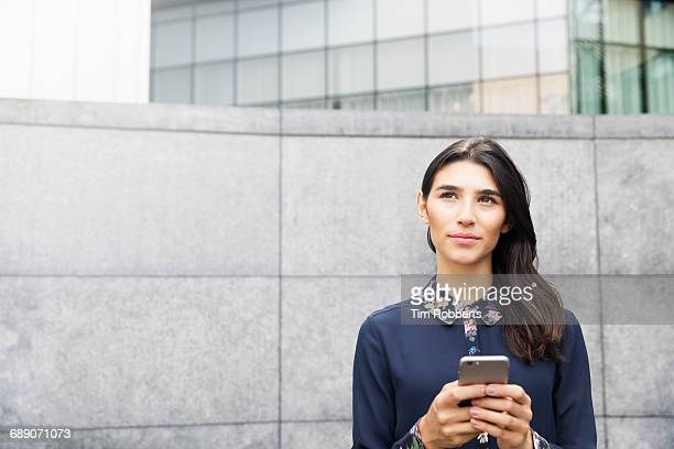 woman looking up with mobile phone. - choice stock pictures, royalty-free photos & images