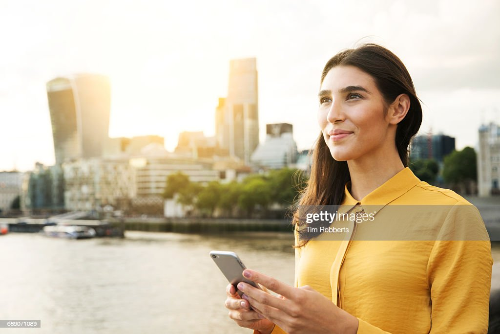Woman looking up with mobile phone, sunset : Stock Photo
