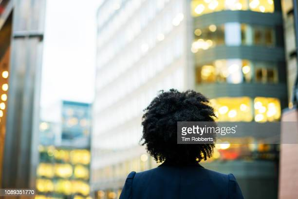 woman looking up with office buildings - afro foto e immagini stock