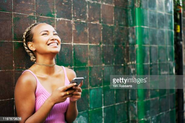 woman looking up with phone next to tiled wall - city life stock pictures, royalty-free photos & images