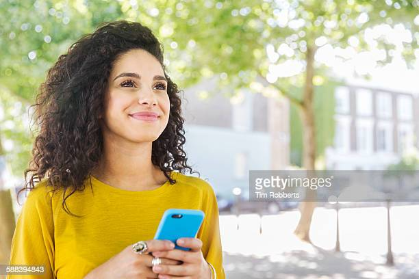 woman looking up with smart phone - curly stock pictures, royalty-free photos & images