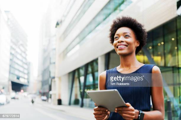 woman looking up with tablet - equipment stock pictures, royalty-free photos & images