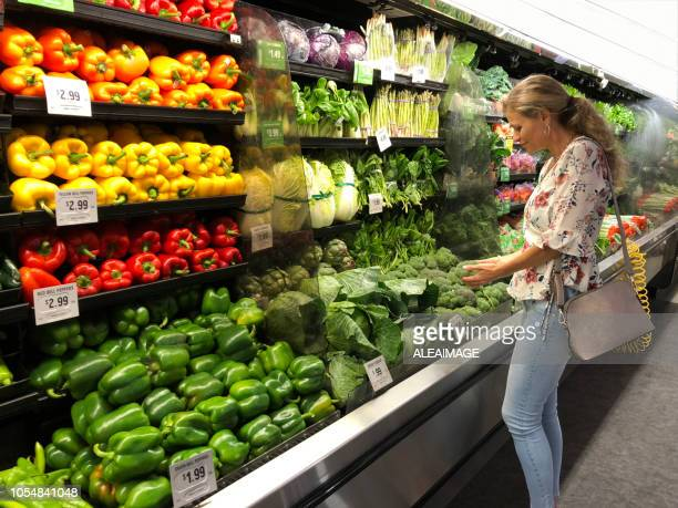 woman looking vegetables - produce aisle stock photos and pictures
