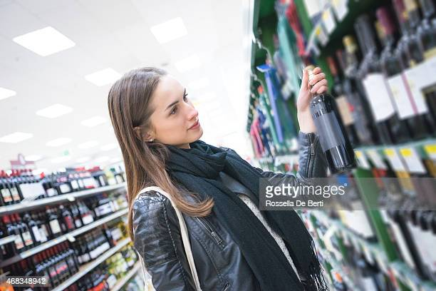 Woman Looking Wine Bottles