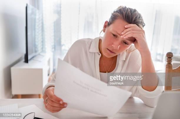 frau schaut besorgt halten papiere zu hause. - geld und finanzen stock-fotos und bilder