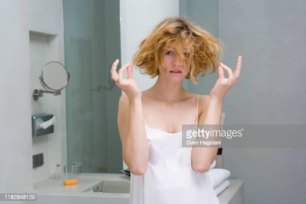 woman looking worried in bathroom - capelli donna foto e immagini stock