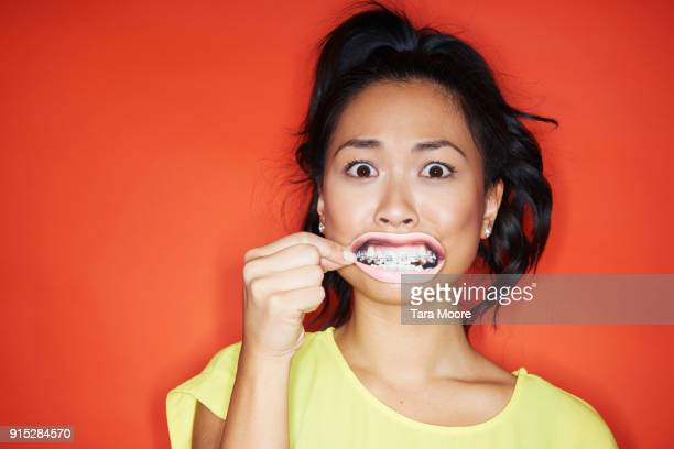 woman looking worried - braces stock photos and pictures