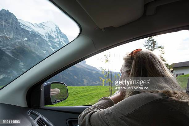Woman looks across mountain meadow from car door