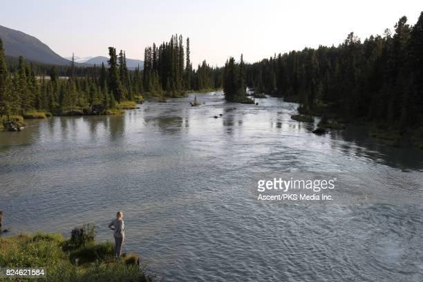 Woman looks across river from shoreline rocks, mountains