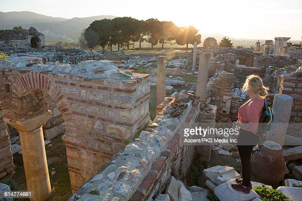 Woman looks across ruin and ancient columns