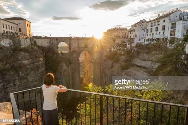 woman looks across to village from railing - local landmark stock pictures, royalty-free photos & images