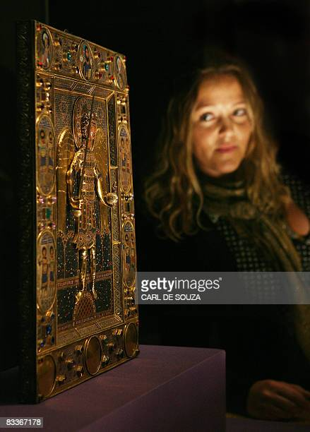 A woman looks at a 12th Century enamel icon of the Archangel Michael at the Entrance to Paradise at the Royal Academy of Arts in London on October 21...