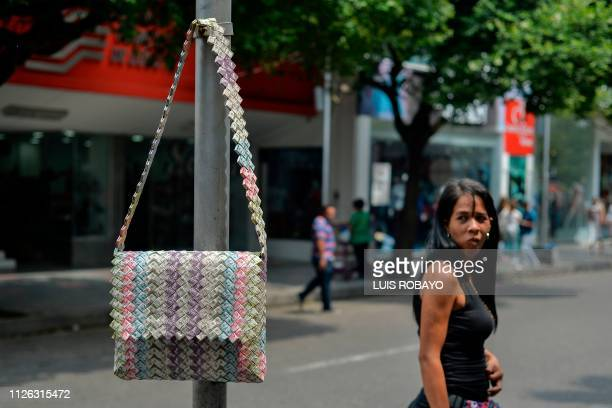 A woman looks at a bag made with Bolivar bills displayed for sale in a street of Cucuta Colombia on the border with Venezuela on February 20 2019 The...