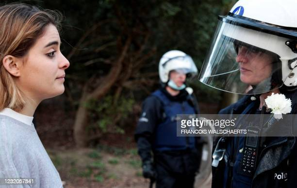 Woman looks at a Belgian police officer wearing a white carnation and standing guard at the Bois de la Cambre parc, in Brussels, on April 1, 2021...