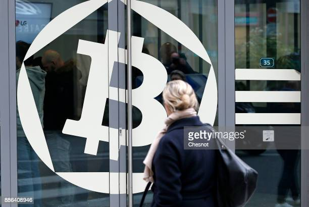 A woman looks at a Bitcoin symbol on a window of the offices of the bank 'La Maison du Bitcoin' on December 05 2017 in Paris France The value of the...