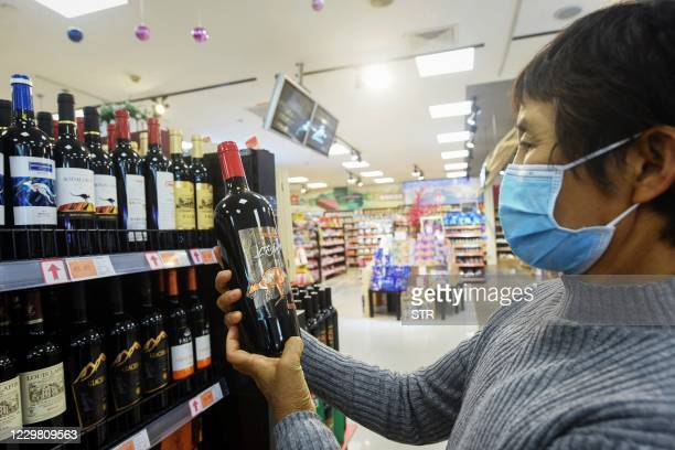 Woman looks at a bottle of Australian wine at a supermarket in Hangzhou, in eastern China's Zhejiang province on November 27, 2020. / China OUT