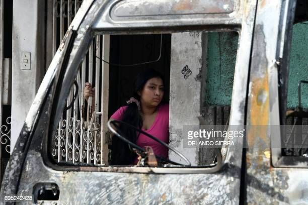 A woman looks at a bus burnt by gang members angry that owners of the companies refuse to pay them a war tax in Comayaguela twin city of Tegucigalpa...