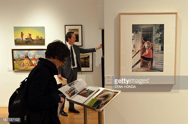 A woman looks at a catalog next to 'Middlebury Vermont 1973' by photographer Nathan Benn in 'The National Geographic Collection The Art of...