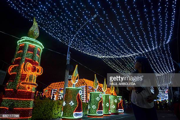 A woman looks at a Christmas light display on December 16 2016 in Medellin Antioquia department Colombia / AFP / RAUL ARBOLEDA