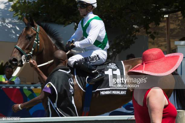 A woman looks at a competitor prior to the Met horse race at Kenilworth race track on January 27 in Cape Town The Met is one of South Africa's...