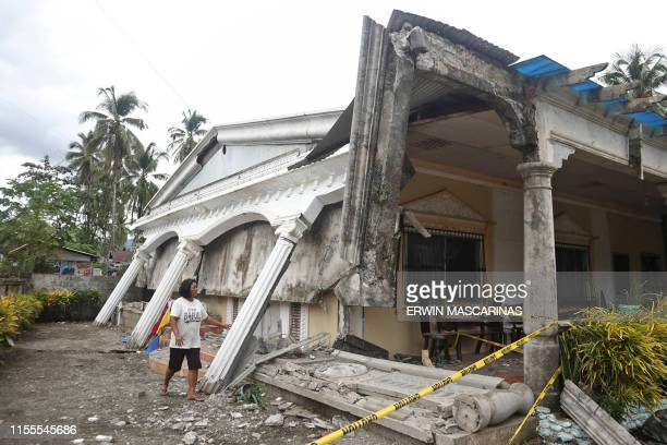 TOPSHOT A woman looks at a destoryed houses after a large earthquake that hit Cantilan Surigao City in southern island of Mindanao on July 14 2019...