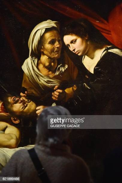 A woman looks at a detail of a painting believed to be the 'Judith Beheading Holofernes' by Italian artist Michelangelo Merisi da Caravaggio...