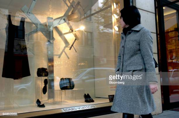 fbc4e9b926022 A woman looks at a dress in the window of Louis Vuitton store in Frankfurt  Germany