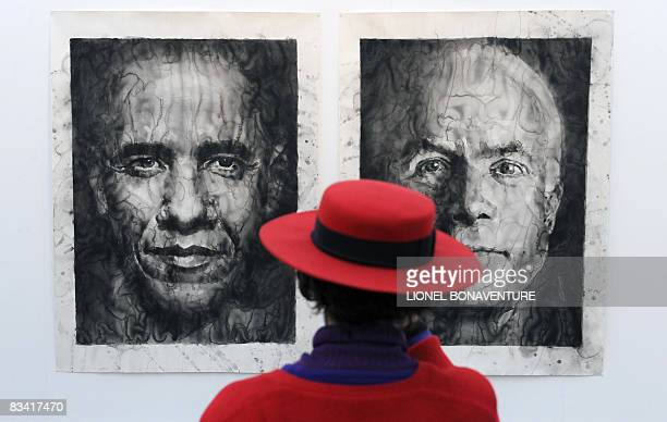 Woman looks at a giant painting figuring US presidential candidates, democrat Barrack Obama and republican John McCain as she visits the fiac...