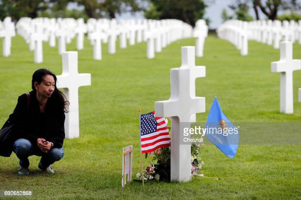 A woman looks at a grave decorated with American Stars and Stripes flag is during commemorations marking the 73th anniversary of DDay at the American...