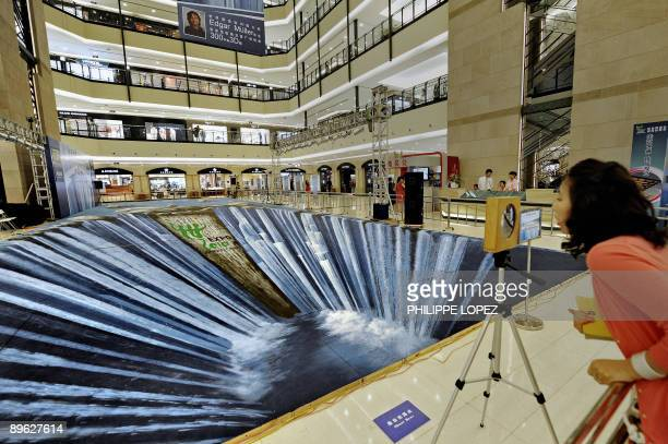 A woman looks at a huge threedimensional painting made on the floor of a shopping mall by German artist Edgar Muller in Shanghai on August 6 2009 The...