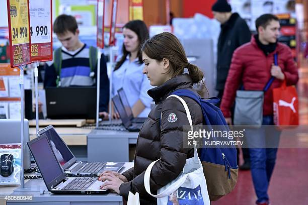 A woman looks at a laptop in a mall in central Moscow on December 15 2014 Russians are feeling the pinch from the slumping ruble but one somewhat...