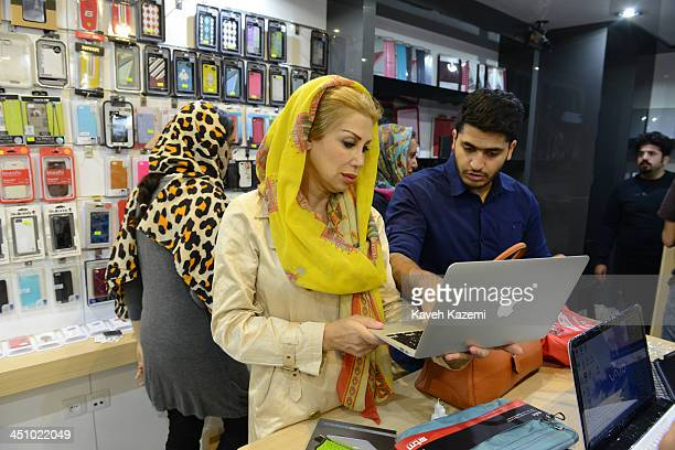 A woman looks at A MacBook Air in a shop specializing in Apple products and smartphone accessories in Paytakht computer mall on October 10 2013 in...