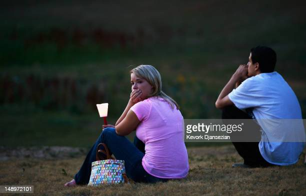 A woman looks at a makeshift memorial after a candelight vigil on July 20 2012 in Denver Colorado The vigil took place across the street from the...