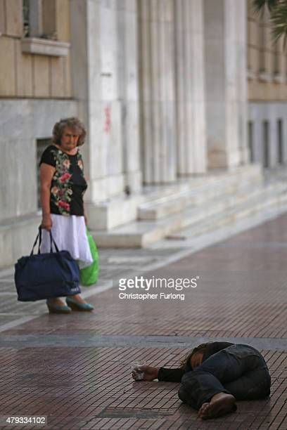 A woman looks at a man begging in front of the Bank of Greece as campaigning on the referendum continues on July 3 2015 in Athens Greece The 'Yes'...