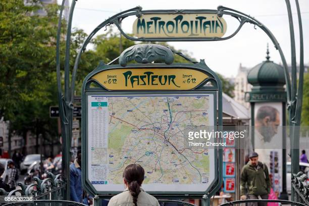 A woman looks at a map of the Paris subway lines at the entrance of the metro station 'Pasteur' on May 22 2017 in Paris France The entrance to this...