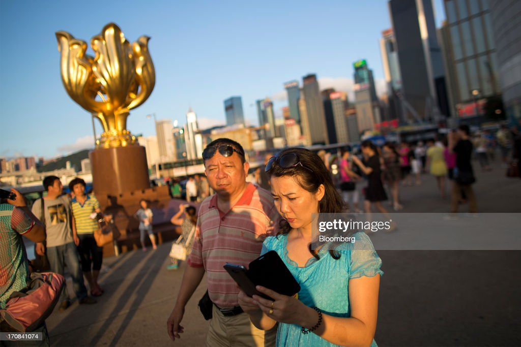 A woman looks at a mobile device as she walks past a sculpture of a gilded bauhinia at Golden Bauhinia Square in Hong Kong, China, on Tuesday, June 18, 2013. A shortage of housing, low mortgage costs and a buying spree by mainland Chinese have led home prices to more than double since the beginning of 2009, shrugging off repeated attempts by the government to curb gains amid an outcry over affordability. Photographer: Jerome Favre/Bloomberg via Getty Images