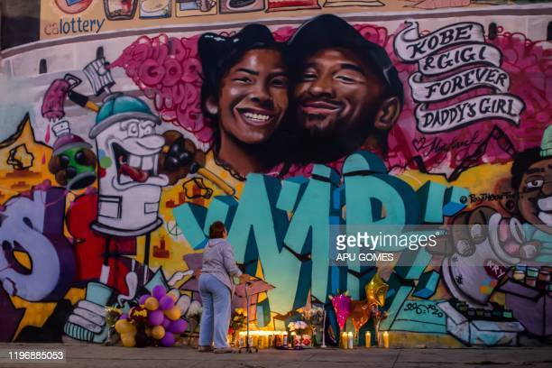 TOPSHOT A woman looks at a mural by the artists Muck Rock and Mr79lts showing Kobe Bryant and his daughter Gianna Bryant who were killed with seven...