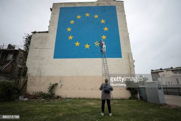 A woman looks at a mural depicting a European Union flag being chiseled by a workman on the side of a disused building near the ferry terminal in...