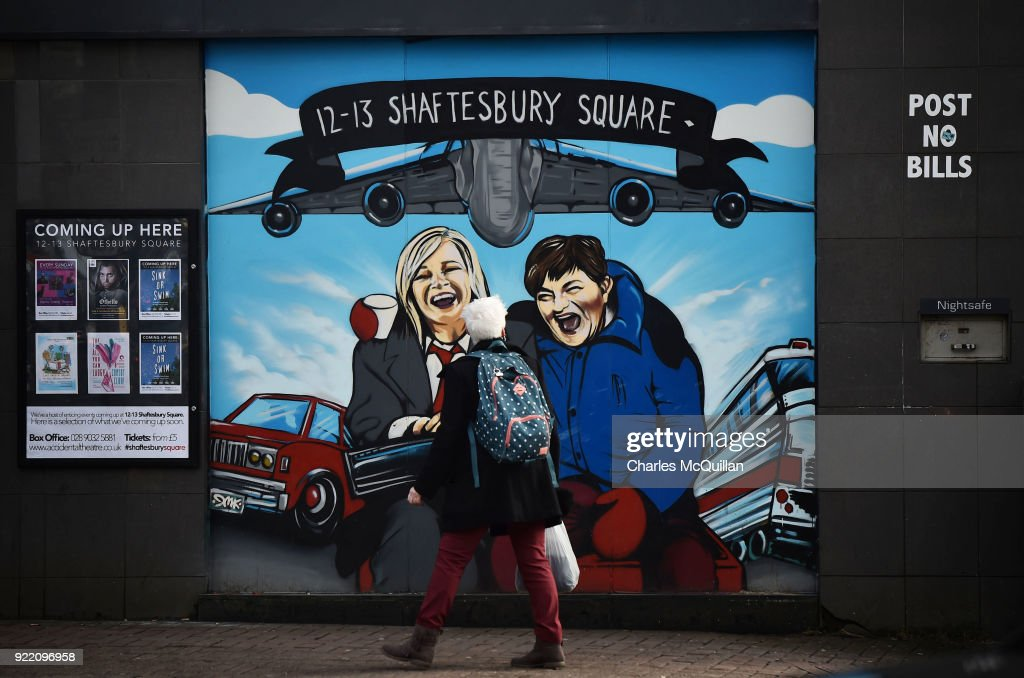 A woman looks at a mural depicting Sinn Fein vice president Michelle O'Neill (L) and DUP leader Arlene Foster as the unlikely bedfellow characters from the movie Planes, Trains and Automobiles on February 21, 2018 in Belfast, Northern Ireland. Talks to restore the Northern Ireland power sharing executive collapsed last week with the main sticking point being a proposed Irish language act. A leaked draft agreement between Sinn Fein and the DUP confirmed a three-stranded approach to the language question, which would have resulted in an Irish language act, an Ulster-Scots act and a so-called respecting language and diversity act. The province has been without a government for over 13 months since then deputy First Minister Martin McGuinness resigned his position in protest at a botched renewable heating scheme.