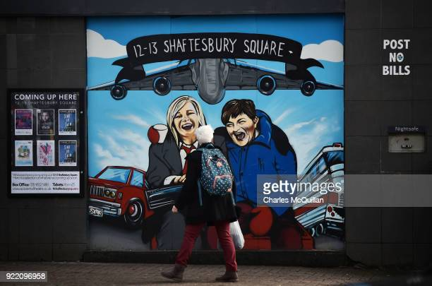 A woman looks at a mural depicting Sinn Fein vice president Michelle O'Neill and DUP leader Arlene Foster as the unlikely bedfellow characters from...